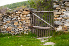 Nieociosana handmade drewniana brama w kamiennej ścianie Fotografia Royalty Free