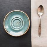 Nieociosana pielucha, łyżka i błękita talerz na czerń łupku naczyniu z kopii przestrzenią dla, twój przepisu lub menu Obrazy Stock
