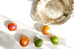 Nieociosana złota taca z narysami i krwionośnymi pomarańczami, wapno na białym marmuru stole Słońce cienie na stole w ranku fotografia stock