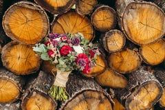 Nieociosany ślubny bukiet z czerwień bzem i różą kwitnie na drewnianym Obrazy Stock