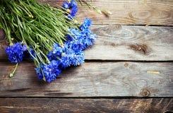 Nieociosany bukiet błękitni cornflowers na rocznik drewnianej desce Obraz Stock