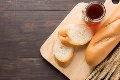 Nieociosany chleb lub baguette z miodem na drewnianym tle Fotografia Stock