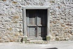Nieociosany drewniany drzwi na kamiennej ścianie Zdjęcie Royalty Free