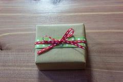 Nieociosany mały prezenta pudełko zawijający w brown Kraft papierze i wiążący z faborkami w łęku Zdjęcie Royalty Free
