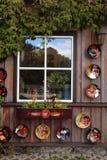 Nieociosany okno z ceramicznymi talerzami i kwiatu garnkiem w drewnianym wiejskim h Obrazy Stock