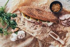 Nieociosany panini na drewnianej desce z czosnkiem, ogórkiem i baleronem, obraz stock