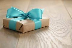 Nieociosany rzemiosło papieru prezenta pudełko z błękitnego faborku łękiem na drewno stole Zdjęcia Stock