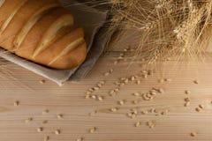 Nieociosany wyśmienicie aromatyczny świeży baguette, bochenek i banatka na drewnianym stołowym copyspace, tekst przestrzeń piec,  fotografia stock