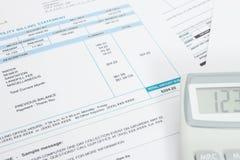 Niepłatny rachunek za usługę komunalną i kalkulator nad nim - zamyka w górę studio strzału Obrazy Royalty Free