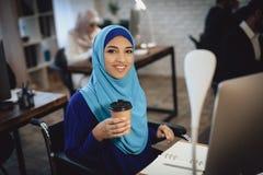 Niepełnosprawna arabska kobieta w wózku inwalidzkim pracuje w biurze Kobieta pracuje na komputerze stacjonarnym i pije kawę fotografia stock