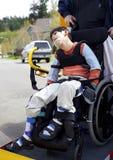 Niepełnosprawna chłopiec na autobusu szkolnego wózka inwalidzkiego dźwignięciu Fotografia Stock
