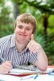 Niepełnosprawna chłopiec robi aprobatom przy biurkiem outdoors fotografia stock