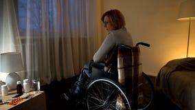 Niepełnosprawna dama czuje osamotnionego siedzącego pobliskiego okno, samotność i beznadziejność, fotografia stock