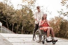 Niepełnosprawna dziewczyna cieszy się przespacerowanie z jej chłopakiem w parku zdjęcie stock