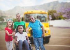 Niepełnosprawna dziewczyna w wózku inwalidzkim z przyjaciółmi przed autobusem szkolnym obraz stock
