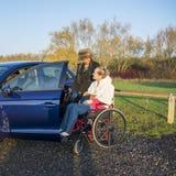 Niepełnosprawna kobieta w wózku inwalidzkim z opiekunem dostaje w ruchliwość samochód zdjęcia stock