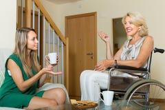 Niepełnosprawna kobieta z gościem przy stołem Zdjęcia Royalty Free