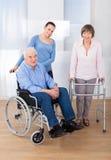 Niepełnosprawna starsza para z opiekunem Zdjęcia Stock