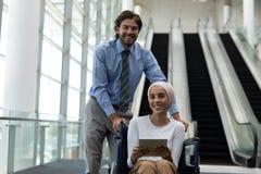 Niepełnosprawnej rasy żeński kierownictwo z Kaukaskim biznesmenem trzyma cyfrową pastylkę w lobby zdjęcie royalty free