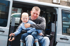 Niepełnosprawni mężczyzna z synem na wózka inwalidzkiego dźwignięciu Fotografia Stock