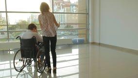 Niepełnosprawny biznesmen na wózku inwalidzkim w okno z rysunkiem na wielkim prześcieradle papier, dyskutuje pracę telefonem zbiory