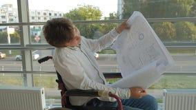 Niepełnosprawny biznesmen na wózku inwalidzkim w okno z rysunkiem na wielkim prześcieradle papier, dyskutuje pracę telefonem zbiory wideo