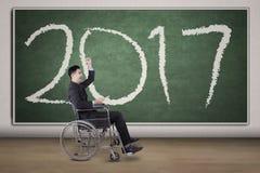 Niepełnosprawny biznesmen patrzeje szczęśliwym z liczbami 2017 Zdjęcie Royalty Free