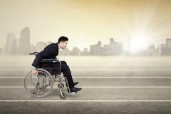 Niepełnosprawny biznesmena dosunięcia wózek inwalidzki outdoors Obraz Royalty Free