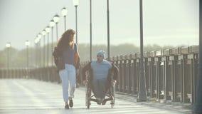 Niepełnosprawny mężczyzna chodzi wpólnie jej dziewczyny na quay w wózku inwalidzkim zbiory