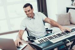 Niepełnosprawny mężczyzna Komponuje piosenkę z Elektrycznym pianinem fotografia stock