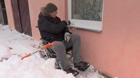Niepełnosprawny mężczyzna na wózka inwalidzkiego cleaning okno od śniegu zbiory