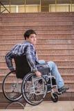Niepełnosprawny mężczyzna na wózku inwalidzkim ma kłopot z schodkami zdjęcia stock