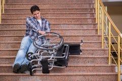 Niepełnosprawny mężczyzna na wózku inwalidzkim ma kłopot z schodkami obraz royalty free