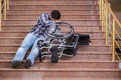 Niepełnosprawny mężczyzna na wózku inwalidzkim ma kłopot z schodkami zdjęcie stock