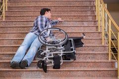 Niepełnosprawny mężczyzna na wózku inwalidzkim ma kłopot z schodkami zdjęcie royalty free