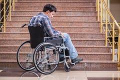 Niepełnosprawny mężczyzna na wózku inwalidzkim ma kłopot z schodkami obrazy stock