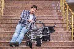 Niepełnosprawny mężczyzna na wózku inwalidzkim ma kłopot z schodkami fotografia stock