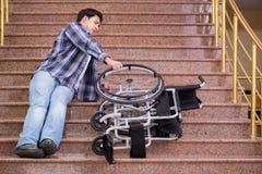 Niepełnosprawny mężczyzna na wózku inwalidzkim ma kłopot z schodkami obrazy royalty free