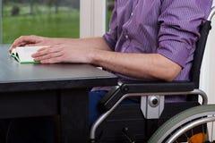Niepełnosprawny mężczyzna obsiadanie, czytanie i Obraz Stock
