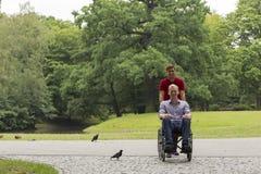 Niepełnosprawny mężczyzna podczas przespacerowania w parku z przyjacielem zdjęcie stock