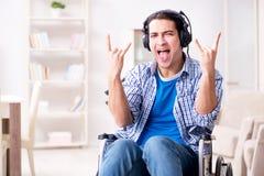 Niepełnosprawny mężczyzna słucha muzyka w wózku inwalidzkim obraz royalty free
