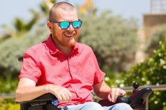 Niepełnosprawny mężczyzna w wózku inwalidzkim cieszy się świeże powietrze przy parkiem Fotografia Royalty Free