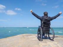 Niepełnosprawny młodego człowieka obsiadanie w wózku inwalidzkim i spojrzenia przy morzem zdjęcie royalty free
