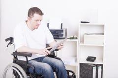 Niepełnosprawny młody człowiek przy biurem Fotografia Royalty Free