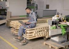 Niepełnosprawny młody człowiek z sztuczną nogą pracuje przy meblarską fabryką zdjęcie stock