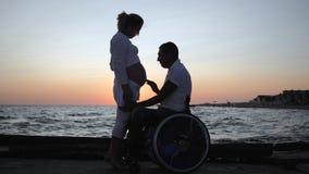 Niepełnosprawny słucha podbrzusze jego żona w wieczór, nieważny współmałżonek w wózku inwalidzkim z ciężarną kobietą przy zmierzc zbiory