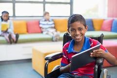 Niepełnosprawny uczeń na wózku inwalidzkim używać cyfrową pastylkę w bibliotece obraz royalty free