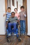Niepełnosprawny uczeń z jego przyjaciółmi w sala lekcyjnej zdjęcia stock