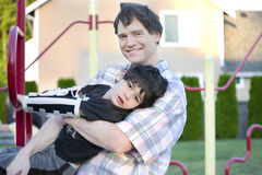 niepełnosprawnego ojca pomaga sztuka boiska syn Fotografia Stock