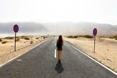 niepewna przyszłość Młodzi samotni kobieta postępy z niepewnym krokiem w pustym asfalcie dezerterują drogę Apokalipsy pojęcie Zdjęcia Stock